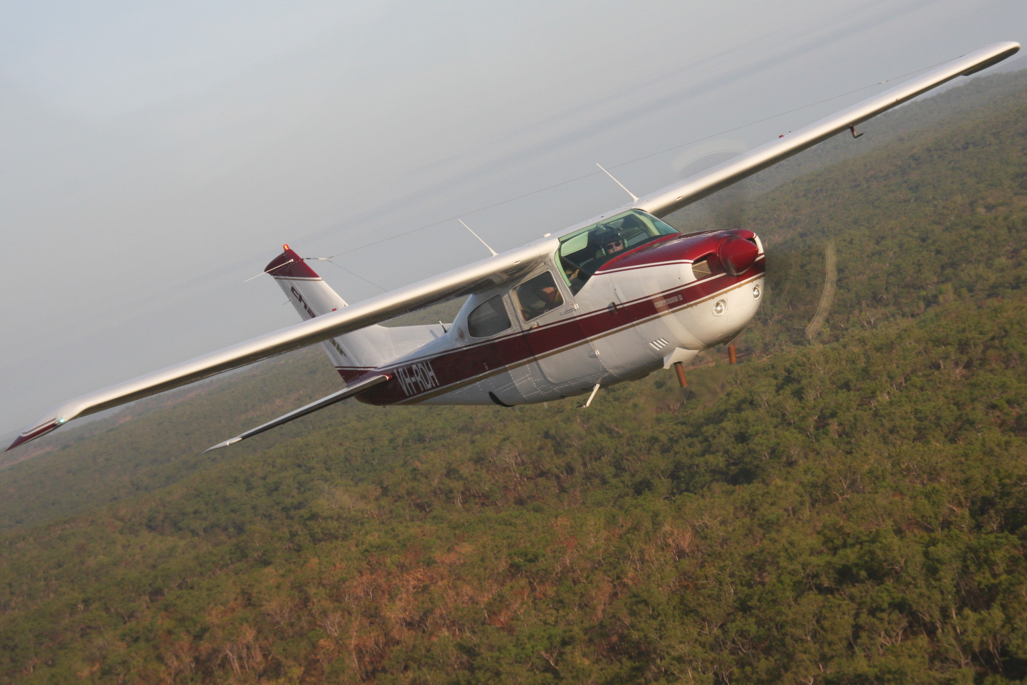 The workhorse of the Top End! A Cessna 210 cuts the horizon on a smokey, dry season day.